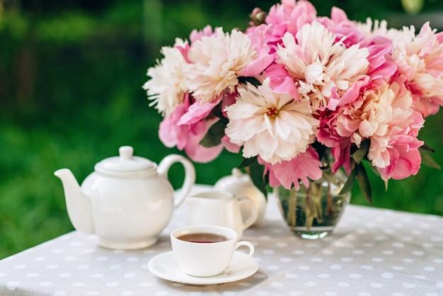 Wazon z kwiatami piwonii przy filiżance kawy