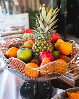 Wazon z owocami z ananasem, jabłkami, gruszkami i kiwi