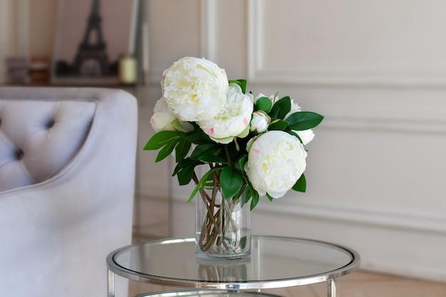 Wazon z pięknymi kwiatami piwonii na stole