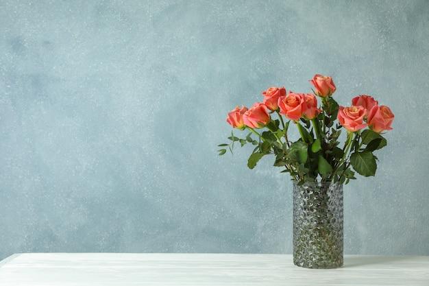 Wazon z pomarańczowymi różami na bielu stole