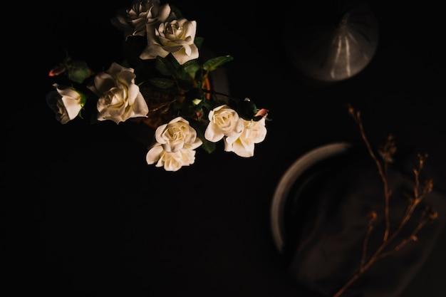 Wazon z różami w pobliżu gałązki