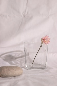 Wazon z różowym suchym kwiatem na stole z białą tkaniną
