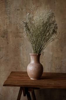Wazon z suchych kwiatów na tle szarej ściany