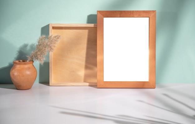 Wazon z suszonymi kwiatami i ramką na zdjęcia na stole