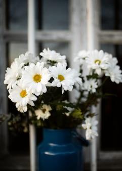 Wazon z wiosennymi kwiatami w oknie