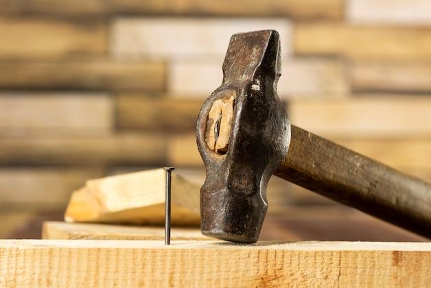 Wbij gwóźdź w drewnianą deskę, prace stolarskie, z bliska wbijanie gwoździa