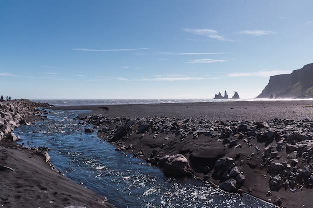 Wbij palce trolla w oceanie w pobliżu plaży z czarnym piaskiem na południu islandii