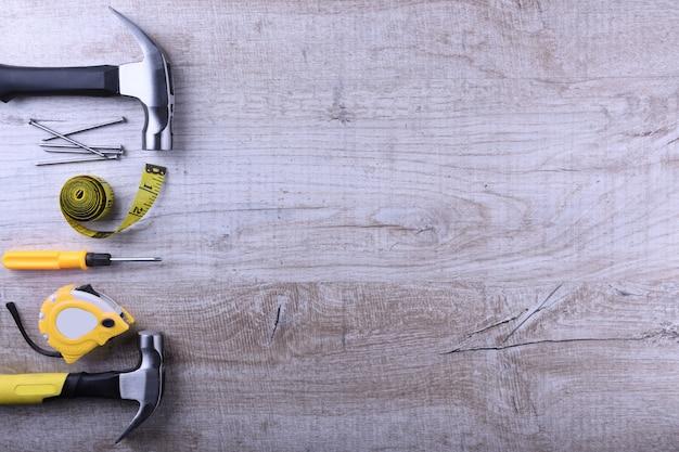 Wbijać żelazo, centymetrową taśmę i gwoździe na drewnianym stole