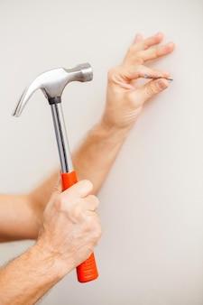 Wbijanie gwoździa. zbliżenie: mężczyzna wbijający gwóźdź