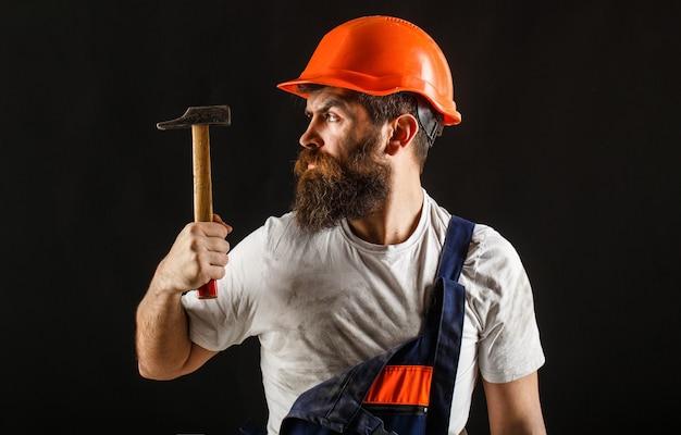 Wbijanie młotka. konstruktor w kasku, młotek, złota rączka, budowniczy w kasku. usługi złotej rączki.