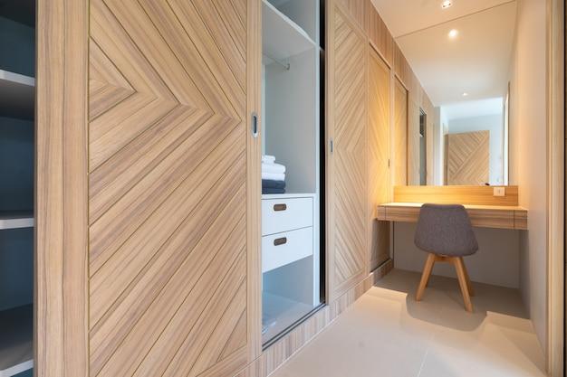 Wbudowana drewniana szafa ze stołem roboczym i krzesłem w sypialni