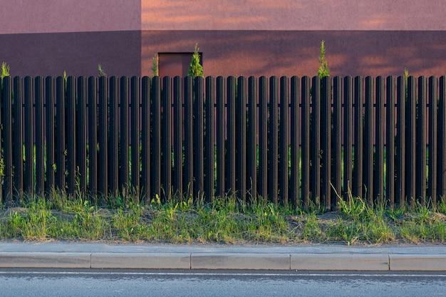 Wbudowane metalowe ogrodzenie, szare i ciemne kolorowe zdjęcie z ulicy