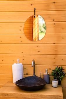 Wc w glampingu. drewniane wnętrze, umywalka, lustro