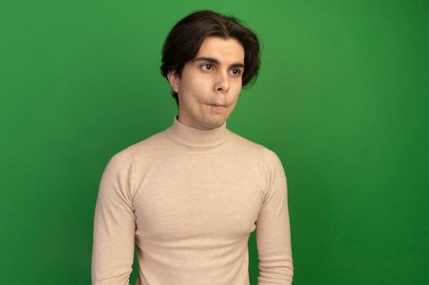 Wciągając usta, patrząc na bok młody przystojny facet na białym tle na zielonej ścianie z miejsca na kopię