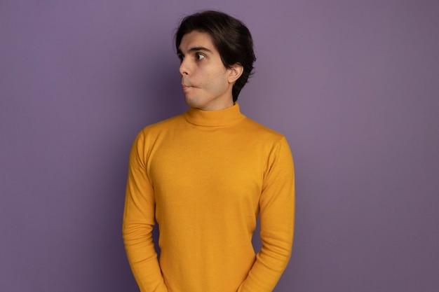 Wciągając usta patrząc na bok młody przystojny facet ubrany w żółty sweter z golfem na białym tle na fioletowej ścianie z miejsca na kopię