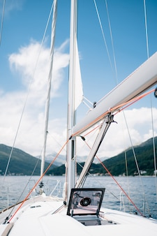 Wciągarka białego jachtu żaglowego z czerwoną liną otwartą szklaną klapą na dziobie statku
