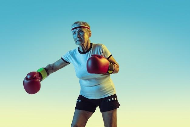 Wciąż kopie. starszy kobieta w boksie sportowym na gradiencie