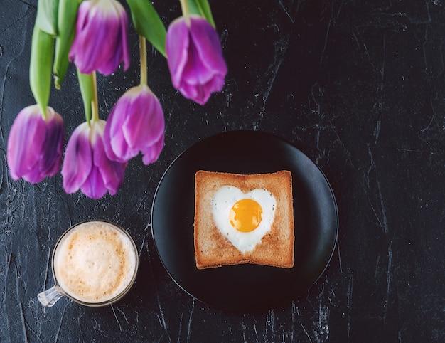 Wciąż śniadanie dla ukochanej osoby z tulipanami na ciemnym tle