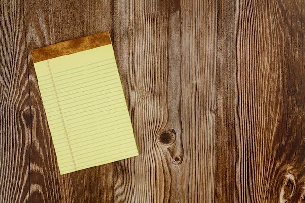 Wciąż życie biznesowe biurowe dostawy z pustym notatnikiem na drewnie zgłaszają tło