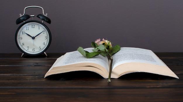 Wciąż życie fotografia wysuszony kwiat na otwartej książce z czarnym alram zegarem