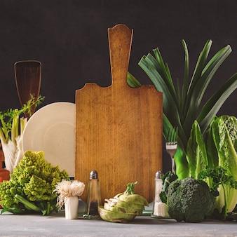 Wciąż życie kuchni deska z świeżymi warzywami na ciemnym tle. koncepcja zdrowej żywności