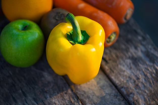 Wciąż życie owoc z żółtą dzwonkowego pieprzu zieloną jabłczaną marchwianą pomarańcze i kiwi na nieociosanym drewnianym tle