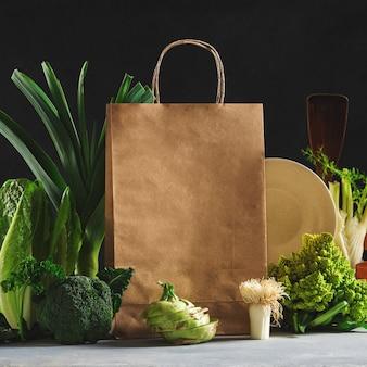Wciąż życie papierowa torba z różnym zdrowym jedzeniem na ciemnym tle