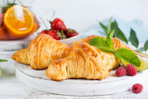 Wciąż życie świezi ranek croissants i jagodowa herbata w szklanym teapot na białym drewnianym tle. pozioma fotografia śniadania. ścieśniać