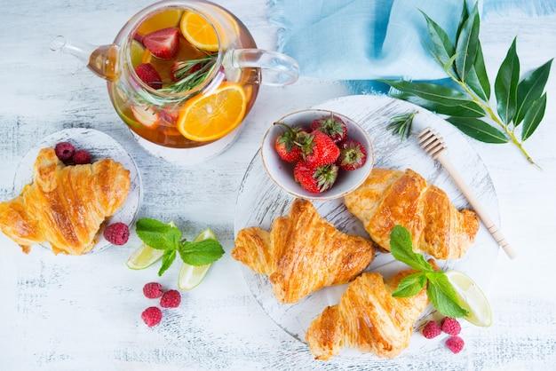 Wciąż życie świezi ranek croissants i jagodowa herbata w szklanym teapot na białym drewnianym tle. pozioma fotografia śniadania. widok z góry