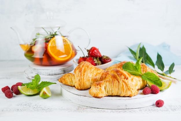 Wciąż życie świezi ranek croissants i jagodowa herbata w szklanym teapot na białym drewnianym tle. pozioma fotografia śniadania.