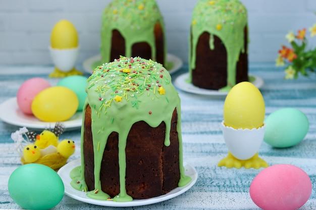Wciąż życie wielkanocni torty i malujący jajka na błękitnym tle