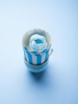 Wciąż życie z błękitnymi filiżankami i kwiatem