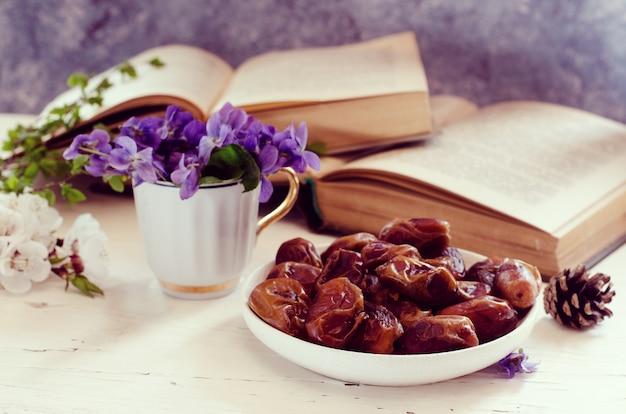 Wciąż życie z fiołkiem w białej filiżance, starych książkach i daktylowych owoc w talerzu. romantyczny kwiatowy