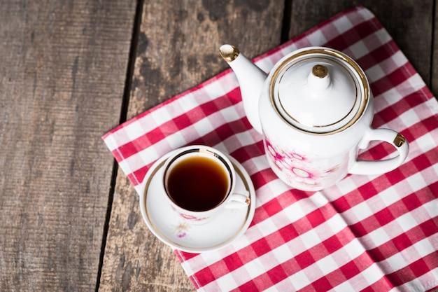 Wciąż życie z herbacianą filiżanką i obrusem na drewnianym stole