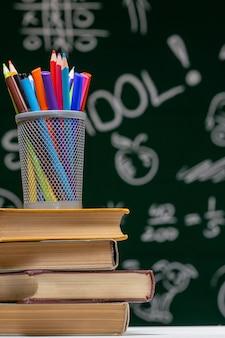 """Wciąż życie z szkolnymi książkami i jabłkiem przeciw blackboard z """"powrotem do szkoły"""" na tle"""