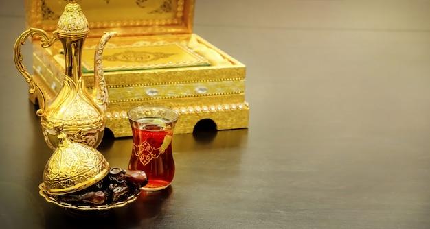 Wciąż życie z tradycyjnym luksusowym złotym arabskim kawowym setem z dallah, filiżanką i datami. księga koranu. koncepcja ramadanu.