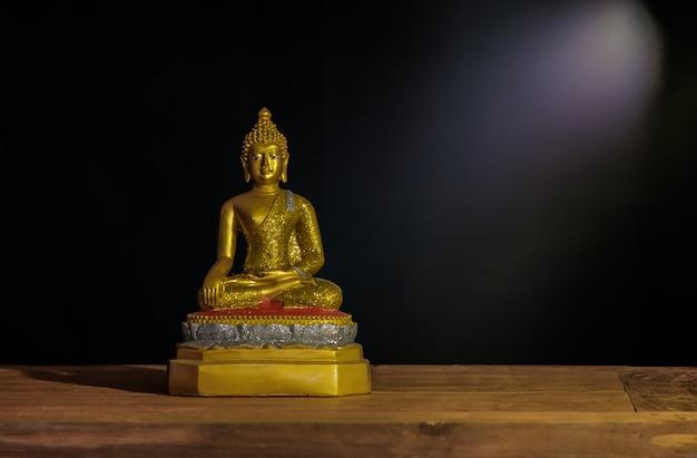 Wciąż życie złota buddha statua z lekkim promieniem.