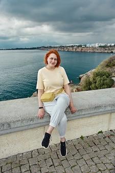 Wczesną wiosną w antalyi młoda europejka siedzi na poręczy punktu widokowego nad morzem