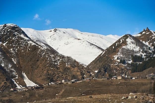 Wczesna wiosna. wioska jest w górach. czapki śnieżne na szczytach gór. mała wioska u podnóża.