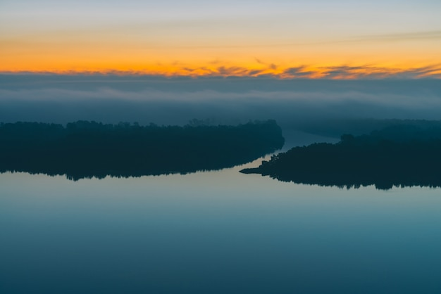 Wczesne błękitne niebo odbite w wodzie rzecznej. brzeg rzeki z lasem pod predawn niebem. żółty pasek w malowniczym niebie. mgła ukryła drzewa na wyspie. kolorowego poranka nastrojowy krajobraz o majestatycznej naturze.