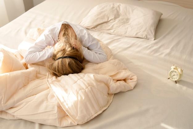 Wcześnie rano dziewczyna siada na łóżku i siada twarzą w dół na poduszce, odmawia chodzenia do szkoły