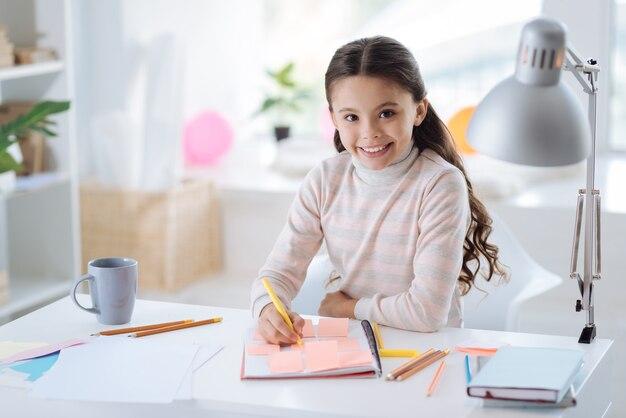 Wczesny rozwój. radosna zachwycona miła dziewczyna uśmiecha się i patrzy na ciebie wykonując swoje domowe zadanie