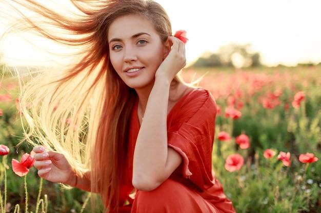 Wdzięczna blondynka zawija się przez ramię i patrzy. wietrzne włosy. malownicze pole makowe w ciepłych barwach zachodzącego słońca.