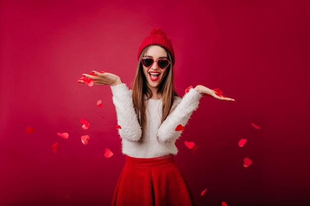 Wdzięczna dziewczyna w puszystym swetrze wyrzuca konfetti serca