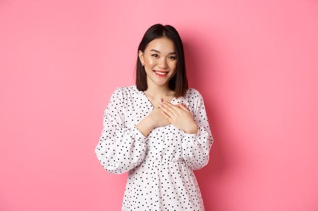 Wdzięczna koreańska dziewczyna w sukience uśmiecha się trzymając ręce na sercu i patrząc z wdzięcznością na dotknięcie kamery ...