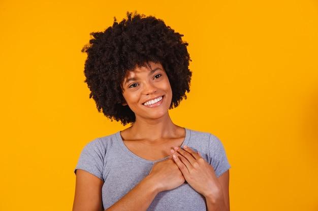 Wdzięczna, pełna nadziei, szczęśliwa czarna kobieta trzymająca się za ręce na klatce piersiowej, czując się zadowolona wdzięczna