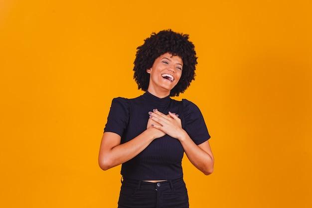 Wdzięczna, pełna nadziei, szczęśliwa czarna kobieta trzymająca się za ręce na klatce piersiowej, czująca się zadowolona, wdzięczna, szczera afrykańska dama wyrażająca szczerą miłość, uznanie, wdzięczność, uczciwość na białym tle na żółtym tle studia