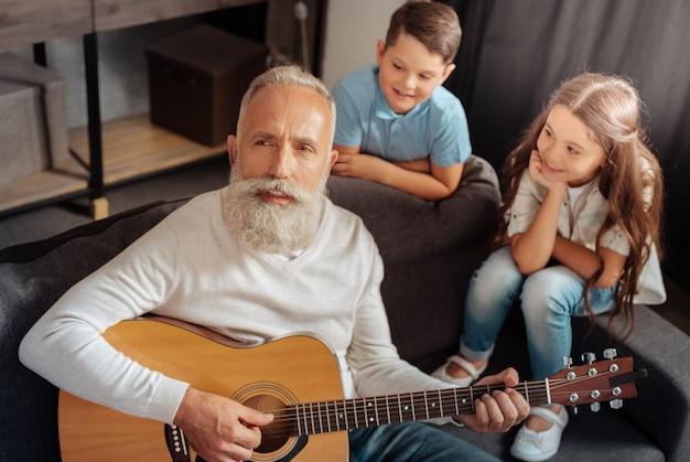 Wdzięczna publiczność. zainspirowany starszy mężczyzna grający na gitarze i śpiewający dla swoich wnuków, którzy słuchają go z podziwem