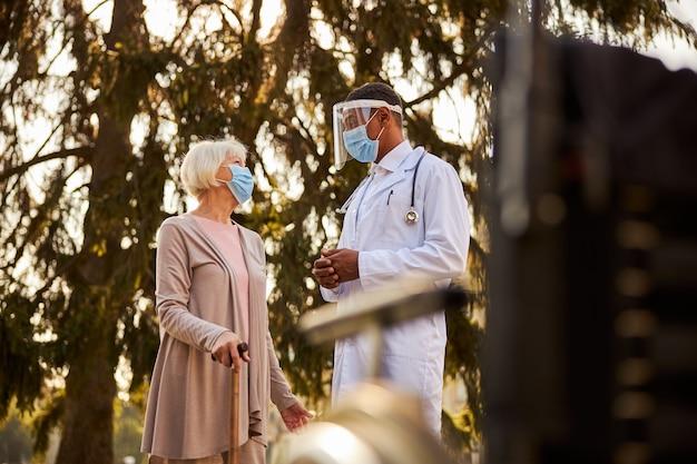 Wdzięczna starsza pani z laską patrząca radośnie na swojego troskliwego lekarza, stojąc wśród drzew