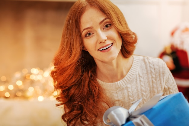 Wdzięczne oczy. zdziwiona rudowłosa kobieta o oczach pełnych zdziwienia po otrzymaniu w domu wielkiego prezentu bożonarodzeniowego.